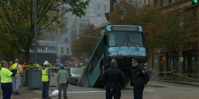 The rear of the bus fell into the sinkhole, leaving the front part sticking up in the air.