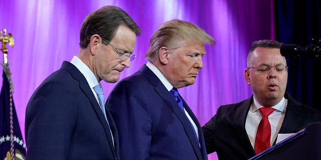 U.S. President Donald Trump prays between Tony Perkins, President of the Family Research Council, and Pastor Andrew Brunson (R) at the Family Research Council's annual gala in Washington, U.S., October 12, 2019.