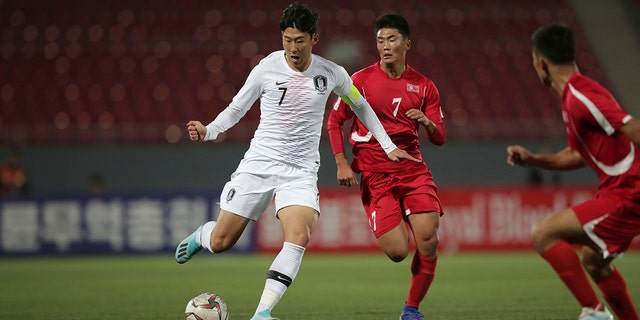 In this photo provided by the Korea Football Association, South Korea's Son Heung-min, left, fights for the ball against North Korea's Han Kwang Song during their Asian zone Group H qualifying soccer match for the 2022 World Cup at Kim Il Sung Stadium in Pyongyang, North Korea, Tuesday, Oct. 15, 2019. (The Korea Football Association via AP).