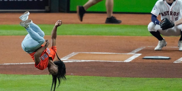 Gymnast Simone Biles does a flip before throwing the ceremonial first pitch before Game 2 of the baseball World Series between the Houston Astros and the Washington Nationals Wednesday, Oct. 23, 2019, in Houston. (AP Photo/Eric Gay)