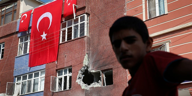 A child stands across from a building damaged by a mortar fired from inside Syra, in Akcakale, Sanliurfa province, southeastern Turkey, Sunday, Oct. 13, 2019. Incoming shells fired from northeastern Syria hit the house earlier on Sunday. Two residents were at the house and were evacuated. (AP Photo/Lefteris Pitarakis)