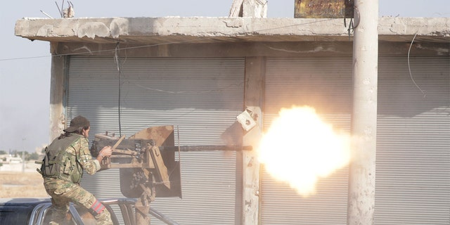 A Turkey-backed Syrian rebel fighter fires a weapon in the town of Tal Abyad, Syria October 13, 2019. REUTERS/Khalil Ashawi - RC16435E4ED0