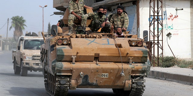 Turkey-backed Syrian rebel fighters ride on a military truck at the border town of Tel Abyad, Syria, on Monday. REUTERS/Khalil Ashawi - RC1A42D723C0