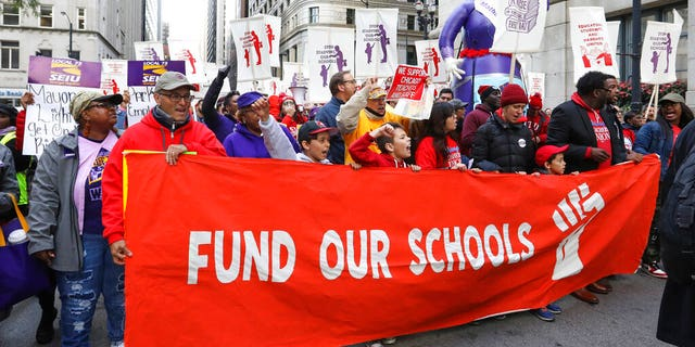 Teachers, staff and their supporters march through downtown Chicago, Monday, Oct. 14, 2019. (AP Photo/Teresa Crawford)