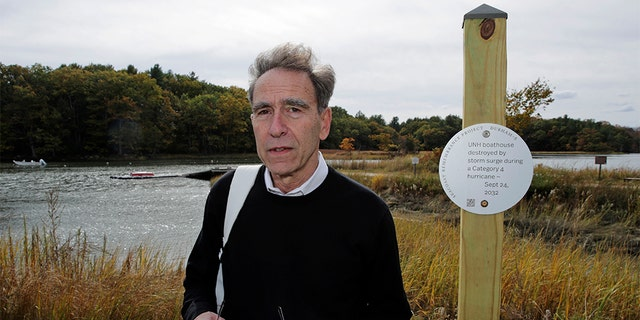 Artist Thomas Starr posing next to a sign on the banks of the Oyster River in Durham, N.H., last week. (AP Photo/Charles Krupa)