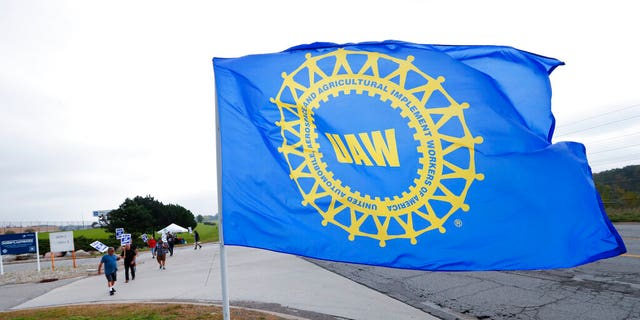 File- In this Sept. 30, 2019, file photo a UAW flag flies near strikers outside the General Motors Orion Assembly plant in Orion Township, Mich. (AP Photo/Paul Sancya, File)