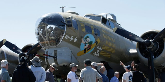 In this photo taken June 2, 2018 photo, people look over the Nine-O-Nine, a Collings Foundation B-17 Flying Fortress, at McClellan Airport in Sacramento, Calif.