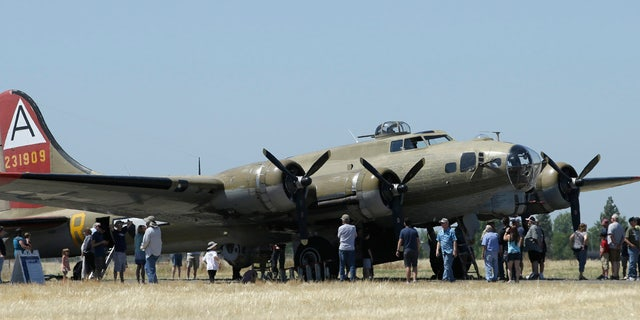 In this photo taken June 2, 2018 photo, people line up to tour the Nine-O-Nine, a Collings Foundation B-17 Flying Fortress, at McClellan Airport in Sacramento, Calif.