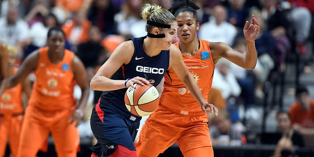 Washington Mystics' Elena Delle Donne, front, drives against Connecticut Sun's Alyssa Thomas during the first half in Game 3 of basketball's WNBA Finals, Sunday, Oct. 6, 2019, in Uncasville, Conn. (AP Photo/Jessica Hill)