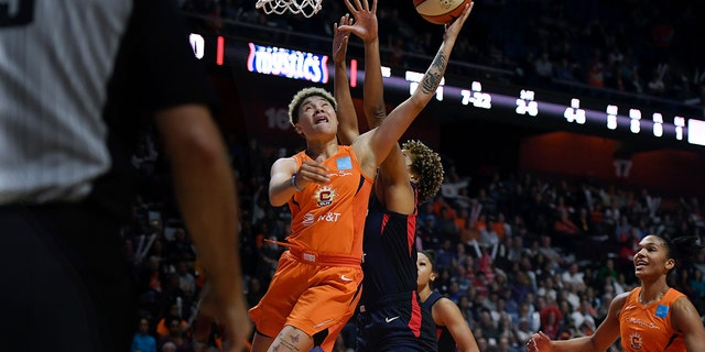 Connecticut Sun's Natisha Hiedeman drives to the basket against Washington Mystics' Tianna Hawkins, rear, during the first half in Game 4 of basketball's WNBA Finals, Tuesday, Oct. 8, 2019, in Uncasville, Conn. (AP Photo/Jessica Hill)