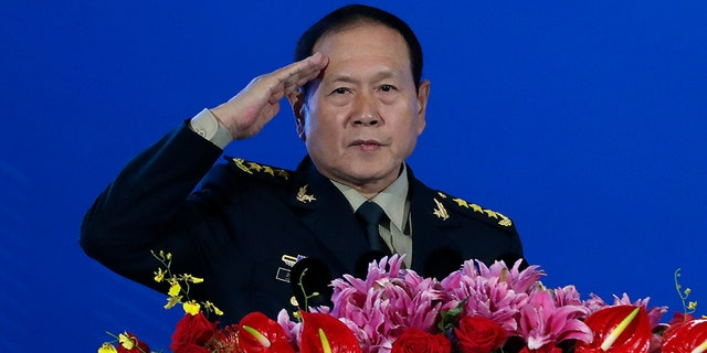 """Chinese Defense Minister Wei Fenghe salutes after delivering his opening speech for the Xiangshan Forum, a gathering of the region's security officials, in Beijing, on Monday. Wei issued a stinging rebuke of the U.S. at a defense forum in Beijing, saying China wasn't fazed by sanctions, pressure and a """"big stick policy."""" (AP)"""