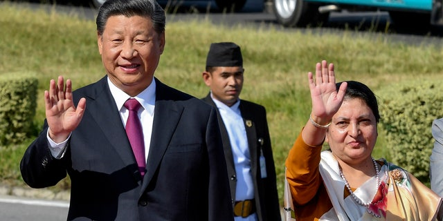 Chinese President Xi Jinping, center left waves with Nepal President Bidhya Devi Bhandari, as he bids farewell, wrapping up his two-day visit to Nepal in Kathmandu, Nepal, Sunday, Oct. 13, 2019.