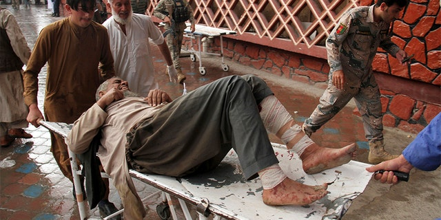 A wounded man is brought by stretcher into a hospital after an explosion at a mosque in Haskamena district of Jalalabad, east of Kabul, Afghanistan, on Friday.