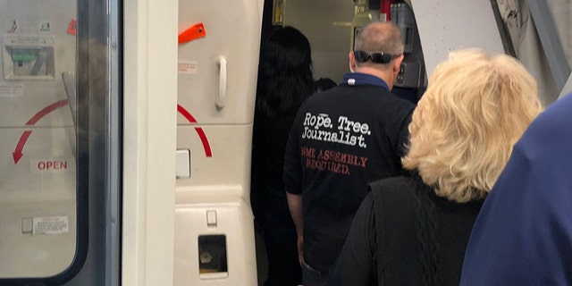 A United Airlines passenger, pictured, was recently spotted wearing聽a T-shirt that alluded to the lynching of journalists on a flight from聽Los Angeles to Boston.