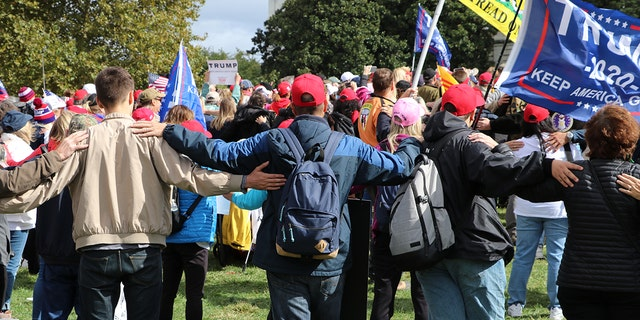 Protesters gather arms at the Trump demonstration on Thursday, symbolically united behind President Trump.