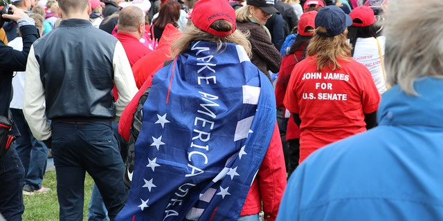 "A woman draped in a ""Make America Great Again"" flag at the March for Trump rally Thursday."