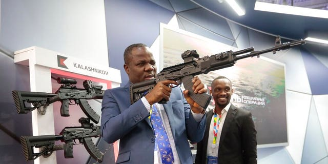 A visitor examines a Kalashnikov weaponry at an exhibition by Kalashnikov company on the sidelines of African countries at the Russia-Africa summit in the Black Sea resort of Sochi, Russia, Thursday, Oct. 24, 2019.