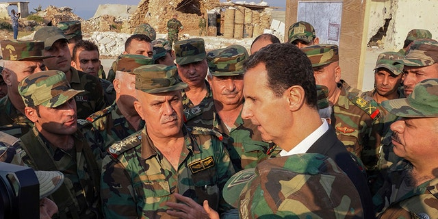 In this photo posted on the official Facebook page of the Syrian presidency, Syrian President Bashar Assad (center right) speaks at his Visit to the city of Habeet in the northwestern province of Idlib (Syria) on Tuesday with Syrian troops. (AP / Facebook page of the Syrian presidency)