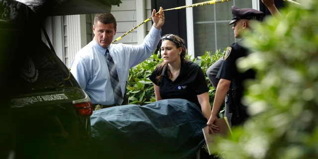 A woman from the Massachusetts Chief Medical Examiners Office, center, uses a gurney to place human remains into a vehicle as law enforcement officers hold caution tape at a home where two adults and three children were found dead with gunshot wounds, Monday, Oct. 7, 2019, in Abington, Mass. (AP Photo/Steven Senne)