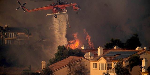 A helicopter drops water while battling the Saddleridge fire in Porter Ranch, Calif., on Friday. (AP)