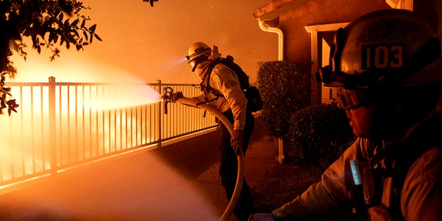 Los Angeles City firefighters conflict a Saddleridge glow nearby homes in Sylmar, Calif., on Thursday.