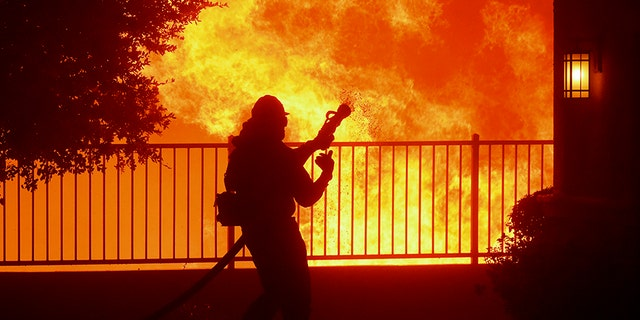 A firefighter waits for water as the Saddleridge fire flares up near homes in Sylmar, Calif.