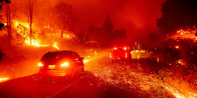 Embers fly across a roadway as the Kincade Fire burns through the Jimtown community of Sonoma County, Calif., on Thursday, Oct. 24, 2019.?