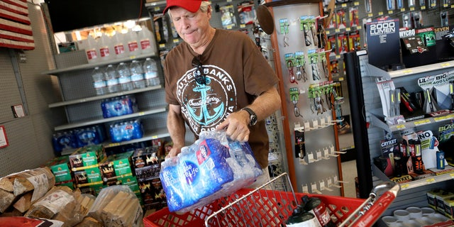 James Cooke is shown buying water bottles along with propane tanks and batteries at a ACE Hardware store as he prepares for a possible power shutdown in Los Gatos, Calif., on Tuesday, Oct. 8, 2019.