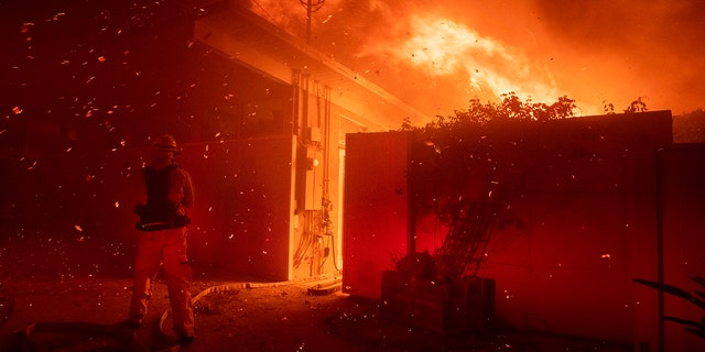 Firefighters try to save a home from a wildfire on Tigertail Road Monday, Oct. 28, 2019, in Los Angeles, Calif.
