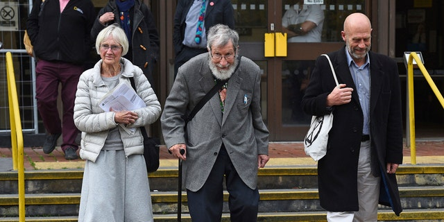 Extinction Rebellion activists Ursula Pethick, aged 83, John Lynes, 91, and John Halladay, 61, leave court where they were bailed to attend trial at a later date charged in connection with an environmental protest, in Folkestone, England, Wednesday Oct. 23, 2019. (Kirsty O'Connor/PA via AP)