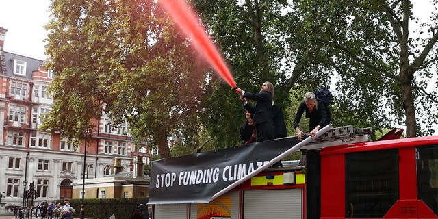 Extinction Rebellion protesters spray a hose outside the Treasury building in London.