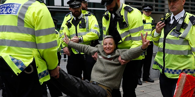 A climate change protester is arrested outside the Home Office in London, Tuesday, Oct. 8, 2019. Police are reporting they have arrested more than 300 people at the start of two weeks of protests as the Extinction Rebellion group attempts to draw attention to global warming. (AP Photo/Alastair Grant)