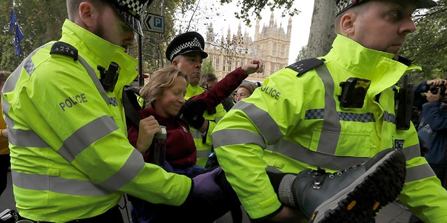 A demonstrator is arrested by police officers during in a climate protest near Parliament in London, Tuesday, Oct. 8, 2019. Police are reporting they have arrested more than 300 people at the start of two weeks of protests as the Extinction Rebellion group attempts to draw attention to global warming. (AP Photo/Kirsty Wigglesworth)