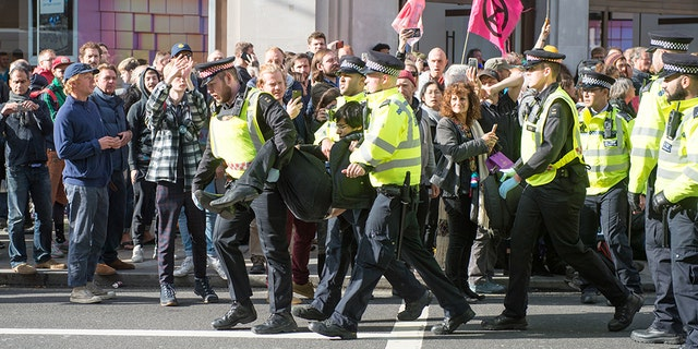 Police arrest an activist as hundreds of members of the Extinction Rebellion environmental activist group swarm Oxford circus with three activists erecting a road blocking wooden pyramid structure with an upside down tree hanging in the middle on October 18, 2019 in London, England.