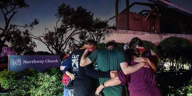 People pray outside Northway Church in Dallas, Texas after a tornado ripped through the community.