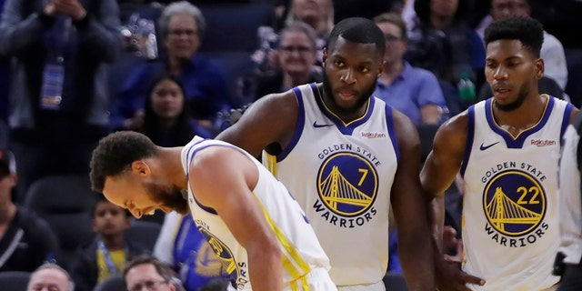 Golden State Warriors' Stephen Curry, left, grimaces as Eric Paschall (7) and Glenn Robinson III (22) watch, after Phoenix Suns' Aron Baynes fell onto Curry during the second half of an NBA basketball game Wednesday, Oct. 30, 2019, in San Francisco. Curry left the game.