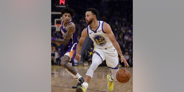 Phoenix Suns' Kelly Oubre Jr., left, guards Golden State Warriors' Stephen Curry during the first half of an NBA basketball game Wednesday, Oct. 30, 2019, in San Francisco.