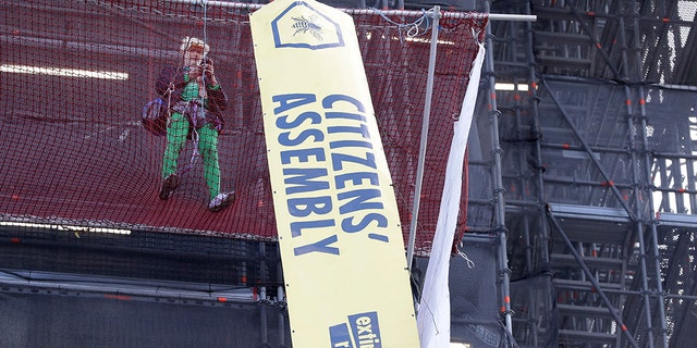 A climate protester demonstrates with banners on the scaffolding covering the Elizabeth Tower that houses the Big Ben clock in London, Friday, Oct. 18, 2019.