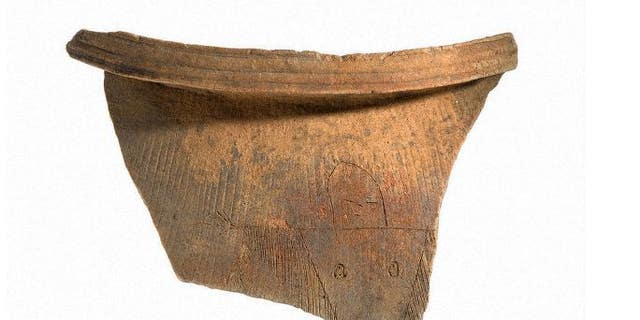 A piece of an earthen vessel with a drawing of a possible female shaman is seen.