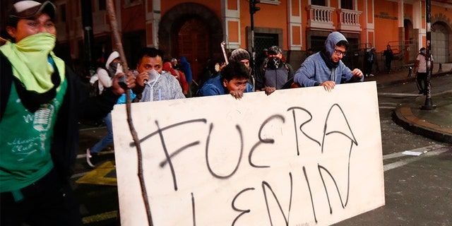 "Protesters cover from tear gas behind a banner which says ""Out Lenin,"" during an anti-government protest in Quito, Ecuador, on Monday. (AP)"