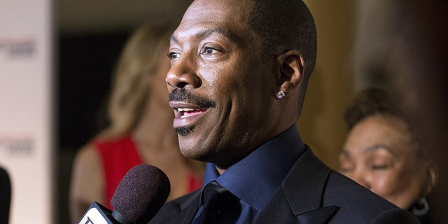 Eddie Murphy speaks to reporters as he arrives for the Mark Twain prize for Humor honoring Murphy at the Kennedy Center in Washington October 18, 2015.