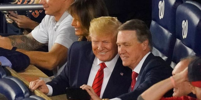 Sen. David Perdue, R-Ga., takes a selfie with President Donald Trump during the seventh inning of Game 5 of the baseball World Series between the Houston Astros and the Washington Nationals Sunday, Oct. 27, 2019, in Washington. (AP Photo/Pablo Martinez Monsivais)