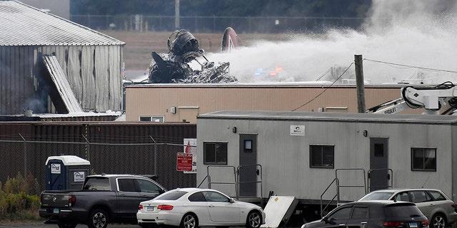 Emergency crews respond after a World War II-era bomber plane crashed at Bradley International Airport in Windsor Locks, Conn., Wednesday, Oct. 2, 2019.
