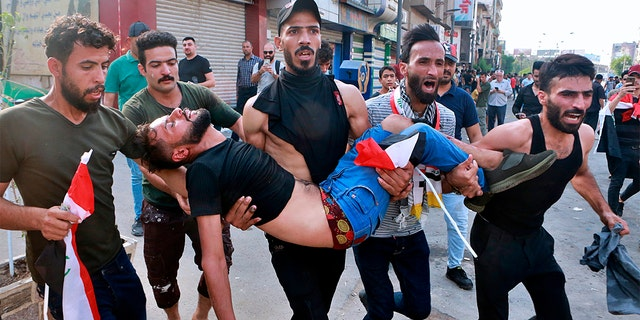 An injured protester is carried off during a protest in Baghdad, Iraq, on Tuesday. (AP Photo/Khalid Mohammed)