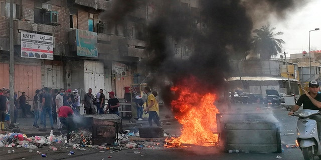 Antigovernment protesters set a fire and block roads in Baghdad on Wednesday. (AP Photo/Hadi Mizban)