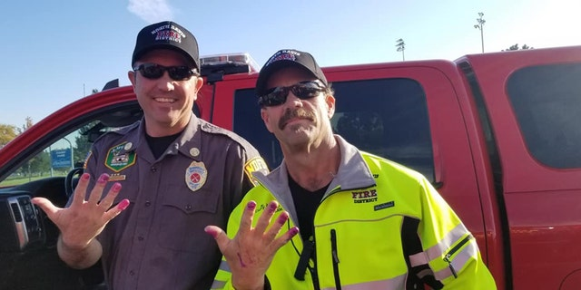 This Friday, Oct. 11, 2019, photo released by the North Davis Fire District shows Chief Allen Hadley, left, and Cpt. Kevin Lloyd In Clearfield, Utah.The two Utah firefighters are receiving praise after they found a creative way to keep a young girl calm at the scene of a car accident.