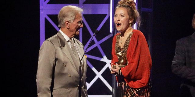 Lauren Daigle, right, accepts the song of the year award from Pat Boone, left, during the Dove Awards on Tuesday, Oct. 15, 2019, in Nashville, Tenn.