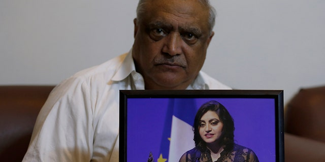 Mohammad Ismail, father of Pakistani human rights activist Gulalai Ismail, holds a picture of his daughter as he poses for a photo in his home in Islamabad, Pakistan, last Thursday.