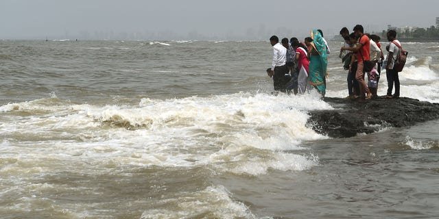 In this photograph taken on September 14, 2019 people gather by the sea during high tide in Mumbai. (PUNIT PARANJPE/AFP/Getty Images)