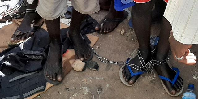 People with chained legs are pictured after being rescued by police in Nigeria